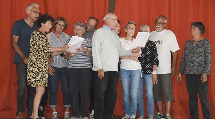 Entouré par des personnes malades, des bénévoles et d'autres aidants, Robert (au centre) fait admirer la justesse de sa voix.